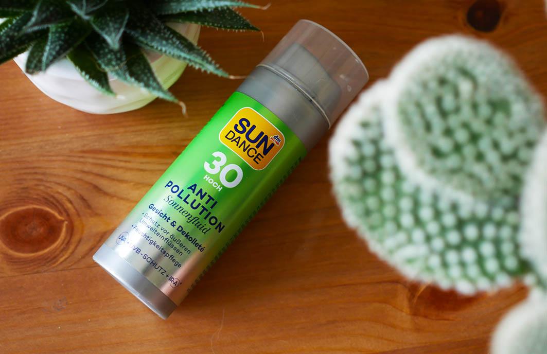 Das grüne Sun Dance Anti-Pollution Sonnenfluid auf Holztisch, umrandet von Pflanzen